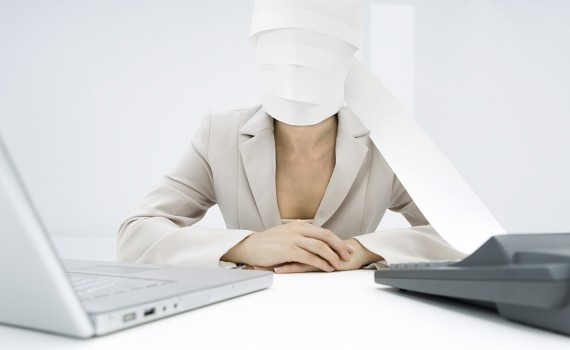 ©Alix Minde/AltoPress/Maxppp ; Professional woman sitting at desk, paper from adding machine wrapped around face